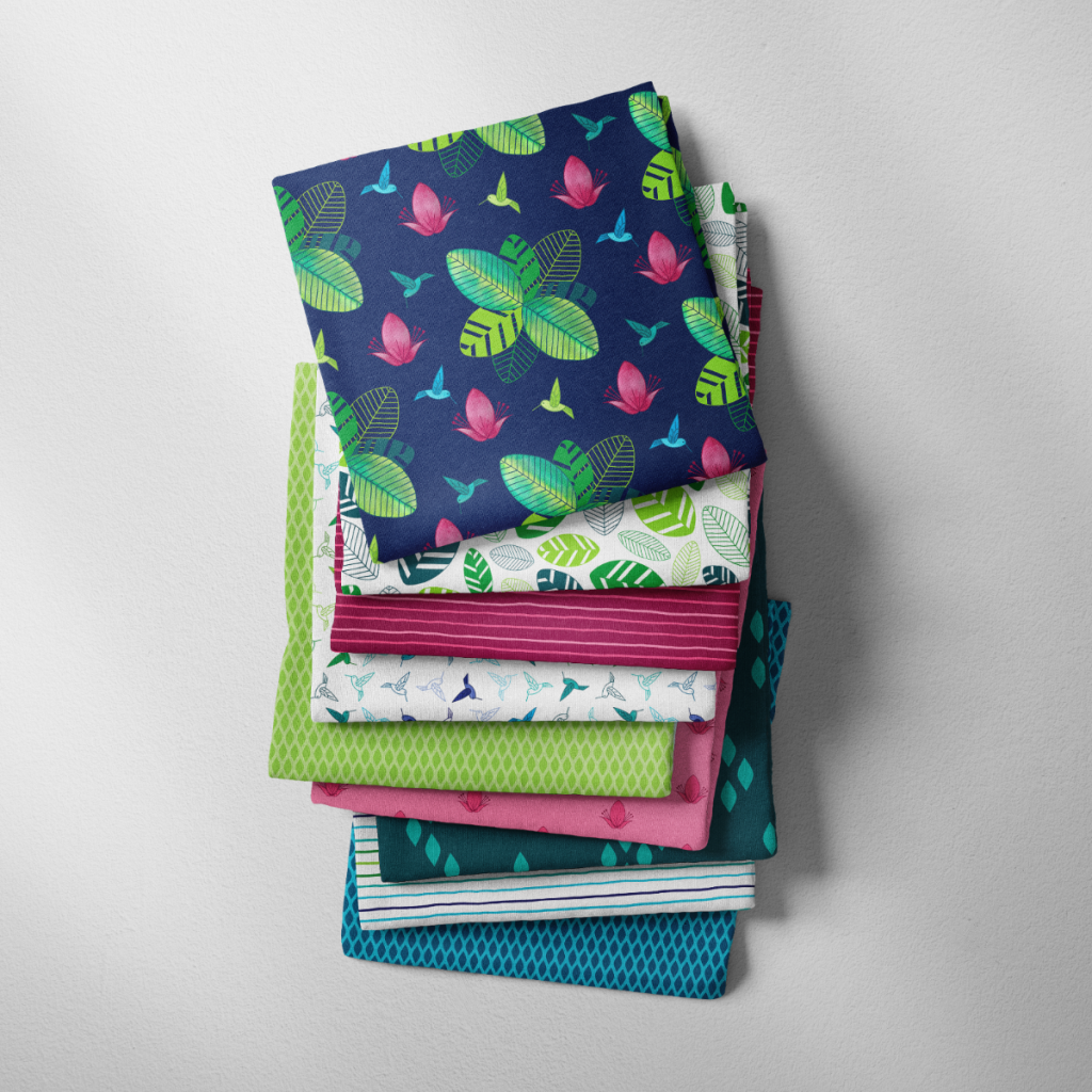 A pile of fabric in various patterns from The Rainforest Joy collection