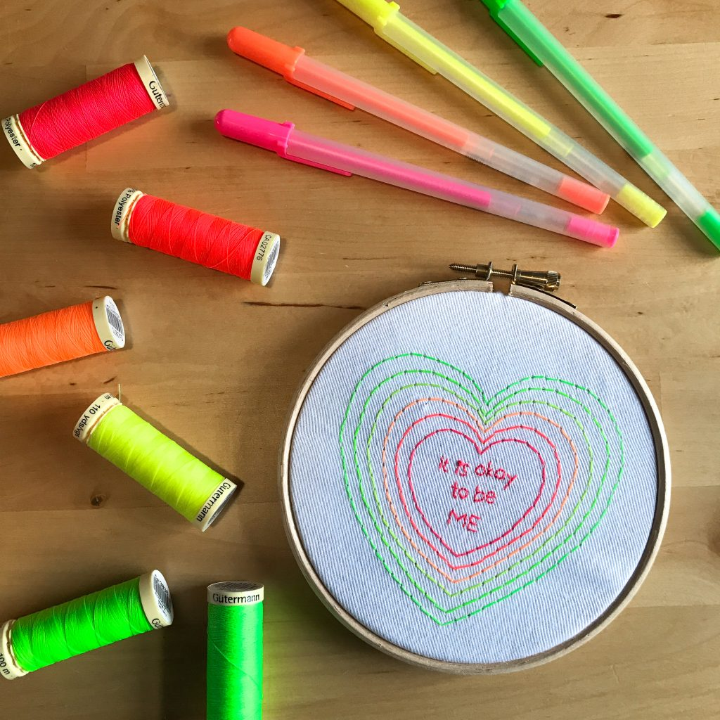 A heart design by @unicornfactoryuk embroidered in neon threads on to white fabric, with the words 'It is okay to be me' embroidered in the centre in neon pink