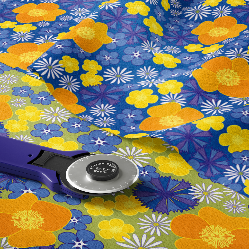 Two versions of wild flowers fabric lying on top of one another, with a blue rotary fabric cutter on top.