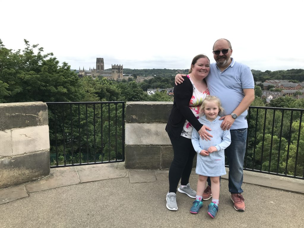 Photo of Helen, her husband and her daughter with Durham Cathedral in the distant background